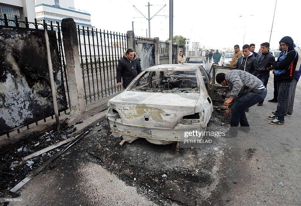 Tunisians inspect a burnt car that was set on fire by protesters following the funeral of assassinated opposition leader Chokri Belaid in Tunis on February 8, 2013. Tunisian police fired tear gas and clashed with protesters as tens of thousands joined the funeral of Belaid whose murder plunged the country into new post-revolt turmoil.