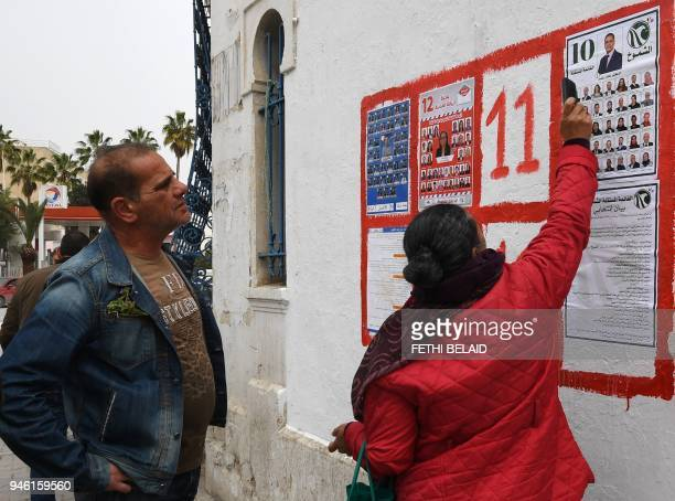 Tunisians look at lists of candidates for the upcoming municipal elections in the Tunis suburb of Ariana on April 14 2018 Tunisia entered an election...