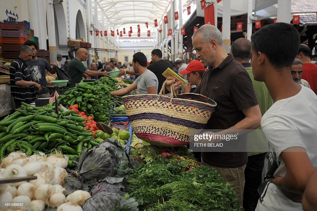 Tunisians look at vegetables displayed on a stall at the central market in Tunis, on June 29, 2014 on the first day of the holy fasting month of Ramadan. Ramadan is sacred to Muslims because it is during that month that tradition says the Koran was revealed to the Prophet Mohammed.