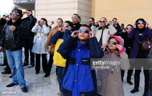 Tunisians observe the world's first partial solar eclipse of 2011 using a telescope on January 4 2011 in Tunis Today's partial eclipse occurred when...