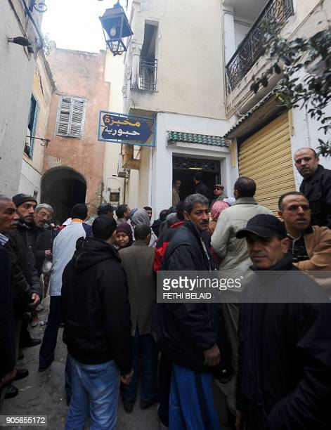 Tunisians queue up to buy some bread in Tunis's Medina on January 16 2011 Dozens of people crowded on Sunday at the few stalls open at the main...