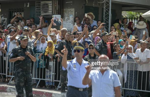 Tunisians wait for the military convoy, carrying the body of Tunisian President Beji Caid Essebsi, died at age 92, from a military hospital to his...