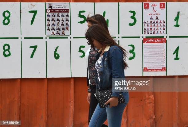 Tunisians walk past lists of candidates for the upcoming municipal elections in the Tunis suburb of Ariana on April 14 2018 Tunisia entered an...