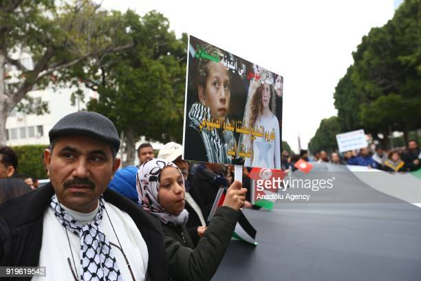 Tunisians wave a Palestinian flag during a protest organized by Tunisians for Palestine Coalition demanding the passage of the proposed law which...