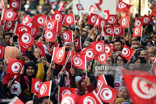 Tunisians wave national flags and shout slogans on January 14 during a rally on Habib Bourguiba Avenue in Tunis to mark the fifth anniversary of the...