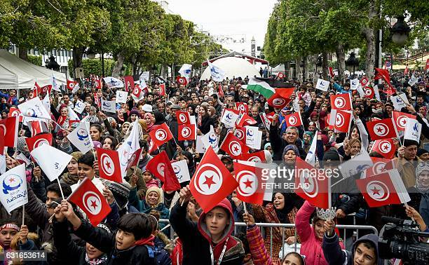 Tunisians wave their national and party flags of the Islamist Ennahdha Party during a rally on January 14 2017 in the Habib Bourguiba Avenue in the...