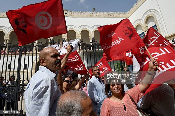 Tunisians wave their national flag and flags bearing the portrait of assassinated leftwing opposition leader Chokri Belaid as demonstrators shout...