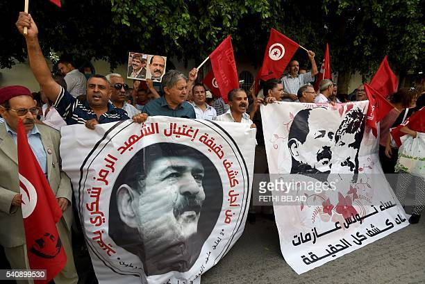 Tunisians wave their national flag and hold posters bearing the portrait of assassinated leftwing opposition leader Chokri Belaid as demonstrators...