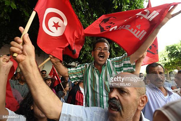 Tunisians wave their national flag and shout slogans against the current Ennahdha Islamist party leader in front of the court in Tunis on June 17...