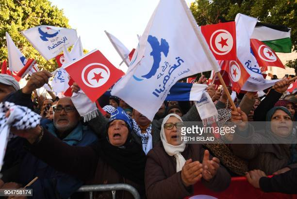 Tunisians wave their national flag and the flag of the Ennahda Islamist party as they gather on Habib Bourguiba Avenue in Tunis on January 14, 2018...