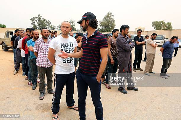 Tunisians who had been detained in Libya by a militia line up at the main administration center for the body that combats illegal migration before...