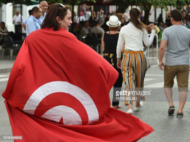 A Tunisians woman wears a national flag during a demonstration to mark Tunisia's Women's Day and to demand equal inheritance rights between men and...