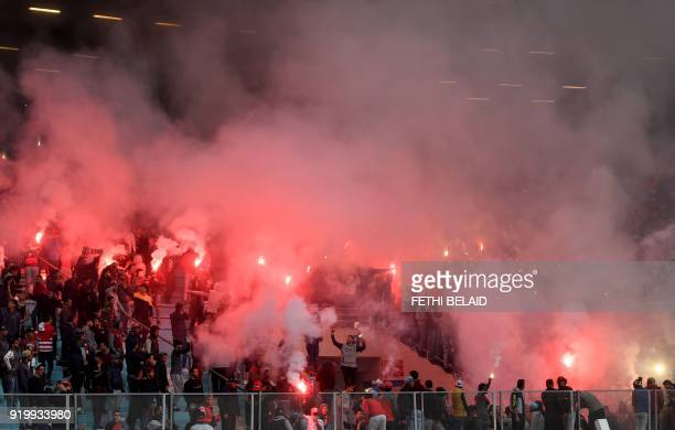 Tunisia's Club Africain fans light flares and cheer during the Tunisia Ligue 1 football match derby between Esperance Sportive de Tunis and Club...