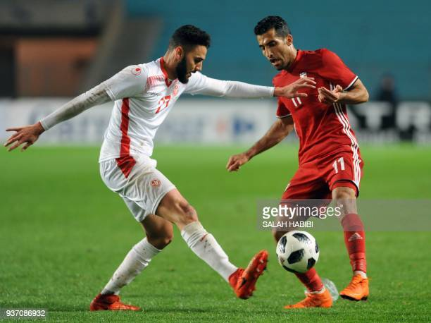 Tunisia's defender Dylan Bronn vies for the ball with Iran's midfielder Vahid Amiri during the international friendly football match between Tunisia...