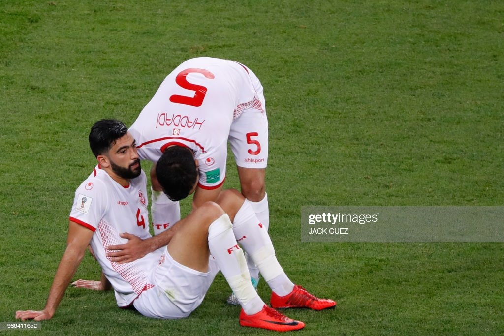 TOPSHOT - Tunisia's defender Oussama Haddadi hugs Tunisia's defender Yassin Meriah at the end of the Russia 2018 World Cup Group G football match between Panama and Tunisia at the Mordovia Arena in Saransk on June 28, 2018. Tunisia won 1-2. (Photo by Jack GUEZ / AFP) / RESTRICTED