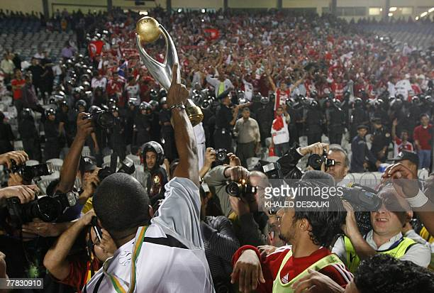 Tunisia's Etoile Sahel player Mejdi Ben Mohamed hold up the trophy in front of Tunisian audience as he celebrates his team's victory a gainst...