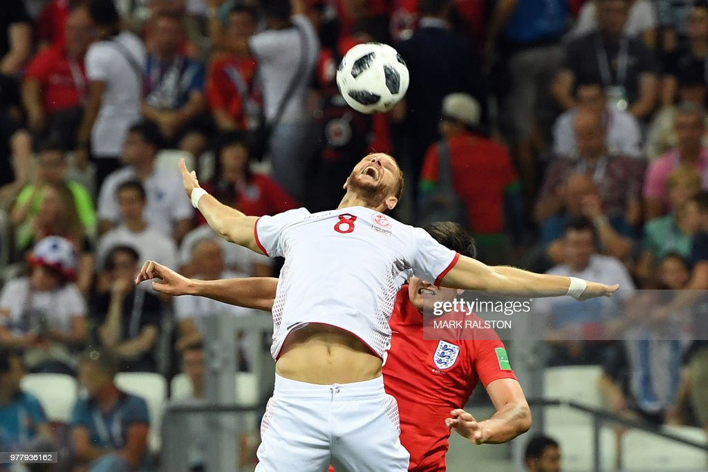 TOPSHOT - Tunisia's forward Fakhreddine Ben Youssef (L) vies with England's defender Harry Maguire during the Russia 2018 World Cup Group G football match between Tunisia and England at the Volgograd Arena in Volgograd on June 18, 2018. (Photo by Mark RALSTON / AFP) / RESTRICTED