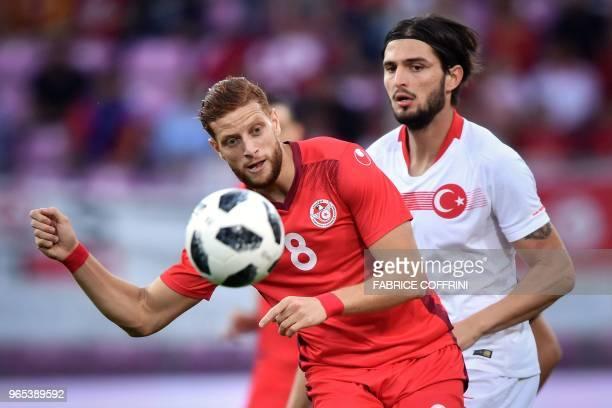 Tunisia's forward Fakhreddine Ben Youssef vies with Turkey's midfielder Okay Yokuslu during the friendly football match Tunisia vs Turkey at the...