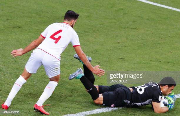 Tunisia's goalkeeper Aymen Mathlouthi makes a save next to Tunisia's defender Yassin Meriah during the Russia 2018 World Cup Group G football match...