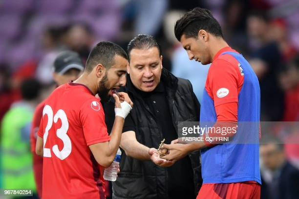 Tunisia's head coach Nabil Maaloul distributes dates to Tunisia's midfielder Naim Sliti and Tunisia's defender Rami Bedoui during the friendly...