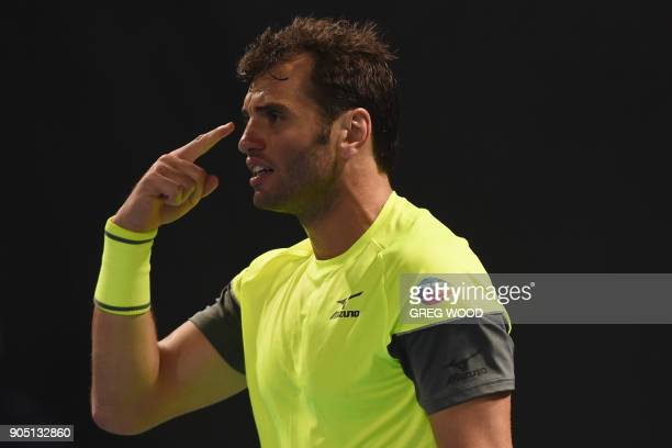 Tunisia's Malek Jaziri gestures as he celebrates after victory over Italy's Salvatore Caruso in their men's singles first round match on day one of...