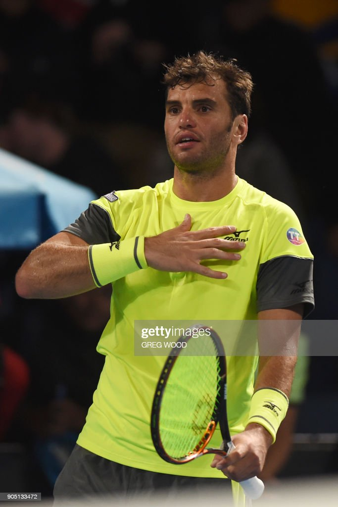 Tunisia's Malek Jaziri gestures as he celebrates after victory over Italy's Salvatore Caruso in their men's singles first round match on day one of the Australian Open tennis tournament in Melbourne on January 15, 2018. / AFP PHOTO / Greg Wood / -- IMAGE