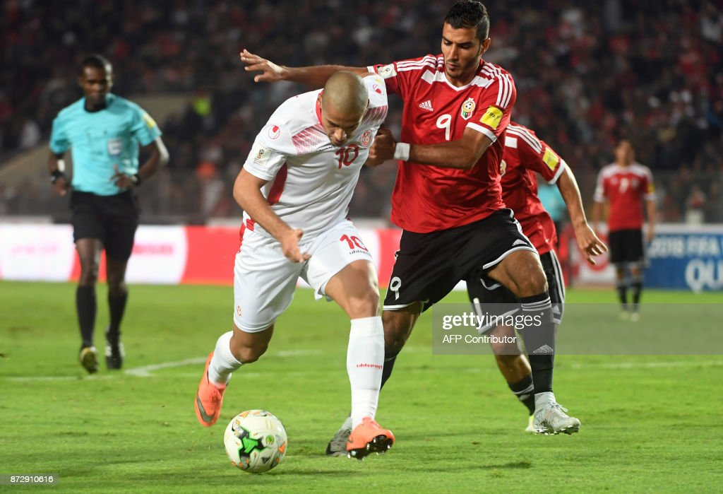 Tunisia's midfielder Wahbi Khazri (L) is marked by Libya's forward Mohamed Al Ghanodi (R) during the FIFA World Cup qualification football match between between Tunisia and Libya at Rades Olympic Stadium on November 11, 2017. /