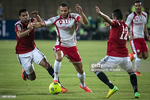 Tunisia's midfielder Yassine Chikhaoui vies for the ball with Egypt's defender Ahmed Fathy and Egypt's midfielder Hazem Emam during the 2015 African...