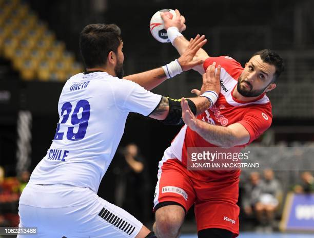 Tunisia's Mohamed Soussi vies with Chile's Marco Oneto during the IHF Men's World Championship 2019 Group C handball match between Tunisia and Chile...