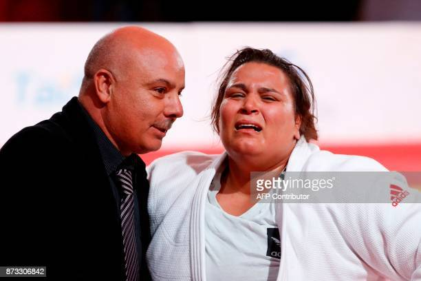 Tunisia's Nihel Cheikh Rouhou celebrates with her coach Rekik Slah after defeating Netherlands' Tessie Savelkouls during their women's Judo World...