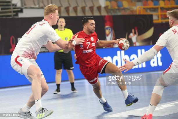 Tunisia's right winger Ramzi Majdoub is challenged by Poland's left back Tomasz Gebala during the 2021 World Men's Handball Championship match...