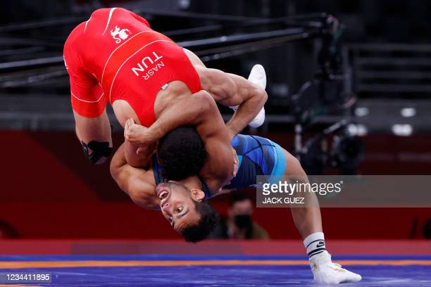 Tunisia's Souleymen Nasr wrestles Refugee Olympic Team's Aker Al Obaidi in their men's greco-roman 67kg wrestling early round match during the Tokyo...