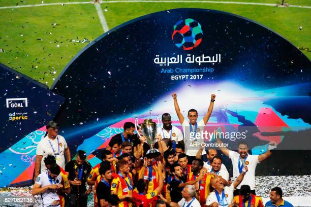 Tuniss Esperance players hold up the trophy as they celebrate their victory over Jordans AlFaisaly in the final match in Arab Club championship at...