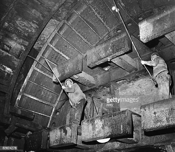 Tunnel diggers known as sandhogs use long poles to reach overhead plates at the most extereme end of the dig as they work on the BrooklynBattery...