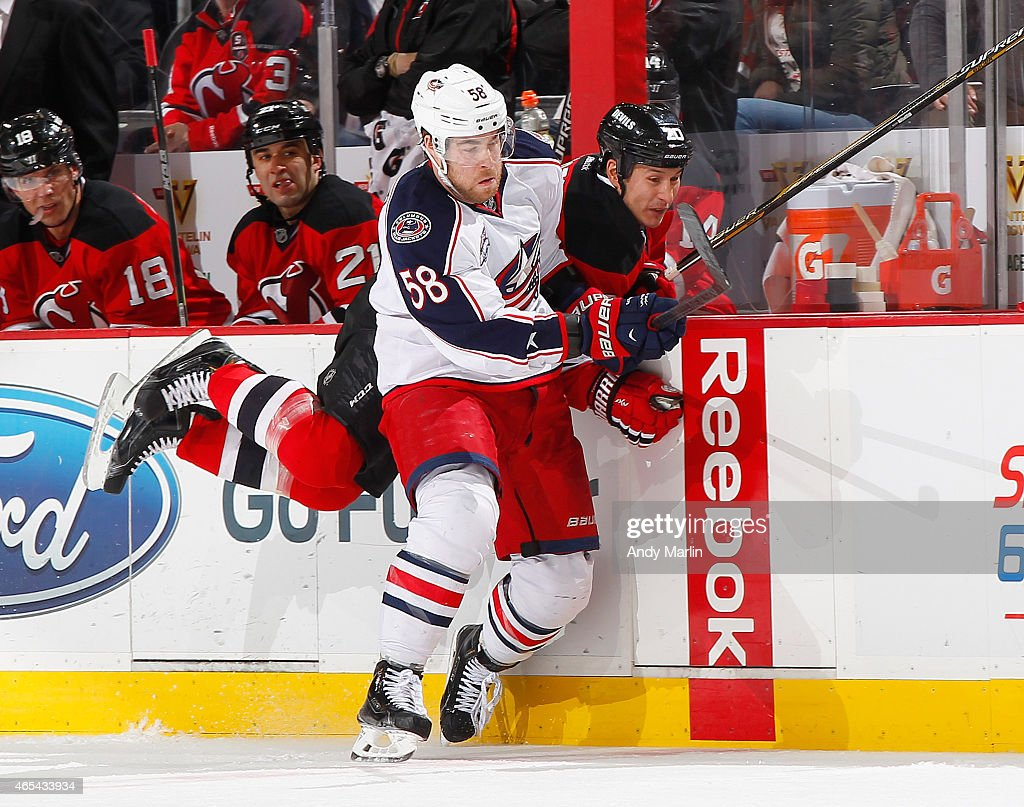 Tuomo Ruutu #15 of the New Jersey Devils is checked into the boards by Marko Dano #58 of the Columbus Blue Jackets during the game at the Prudential Center on March 6, 2015 in Newark, New Jersey.