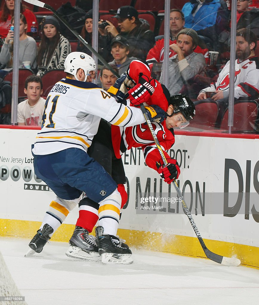 Tuomo Ruutu #15 of the New Jersey Devils is checked near the boards by Andrej Meszaros #41 of the Buffalo Sabres during the game at the Prudential Center on February 17, 2015 in Newark, New Jersey.