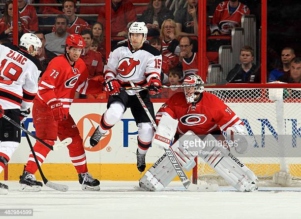 Tuomo Ruutu of the New Jersey Devils jumps out of the way of an oncoming puck as Anton Khudobin of the Carolina Hurricanes looks through the screen...
