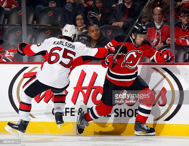 Tuomo Ruutu of the New Jersey Devils skates past Erik Karlsson of the Ottawa Senators during the second period at the Prudential Center on December...