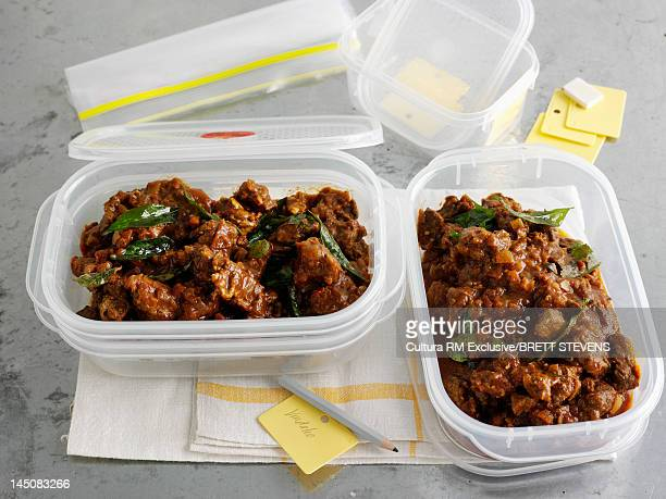 Tupperwares of stewed meat and herbs
