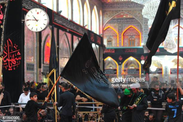 Turbaned cleric checks his cell phone as Shiite pilgrims reach the climax of days of marching inside the shrine of Imam Hossein to commemorate...