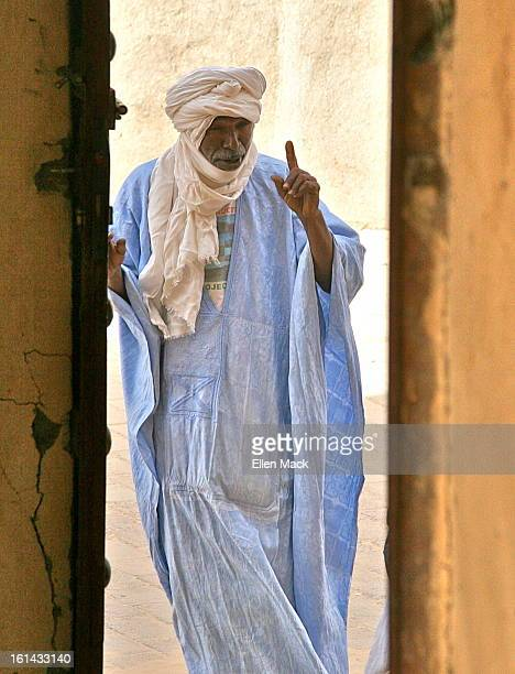 Turbaned man stands in the doorway of one of Timbuktu's famous libraries. He wears the classic clothing of the Tuareg, men of the Sahara Desert