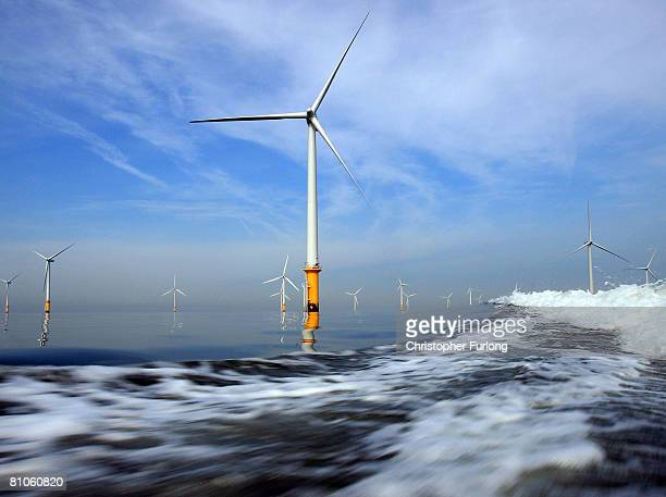 Turbines of the new Burbo Bank off shore wind farm lay in the wake of a maintenance boat in the mouth of the River Mersey on May 12 2008 in Liverpool...