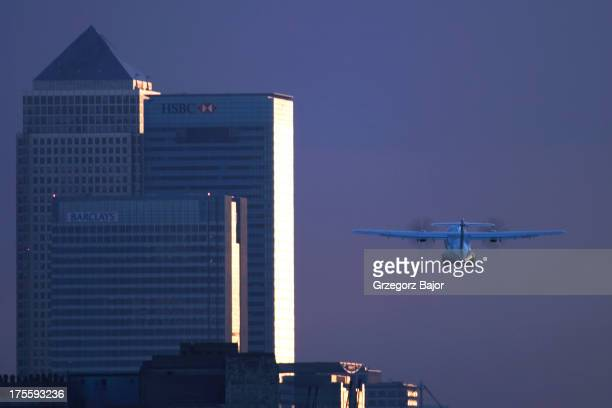 CONTENT] Turboprop aircraft taking off from London City Airport with financial centre and Canary Wharf in the background