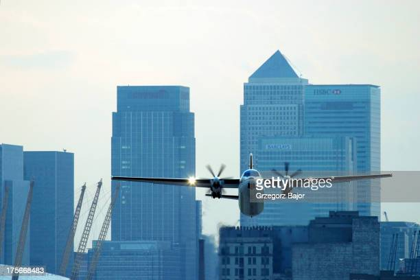 CONTENT] Turboprop regional airliner Fokker 50 taking off from London City Airport with financial centre and Canary Wharf in the background