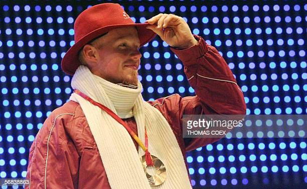 Bronze medallist Latvia's Martins Rubenis celebrates during a 2006 Winter Olympics medal ceremony in Turin 13 February 2006 a day after the singles...