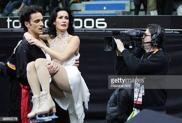 Canadian Patrice Lauzon carries MarieFrance Dubrueil after she felt on the ice during their performance in the Ice Dancing Original Dance event...