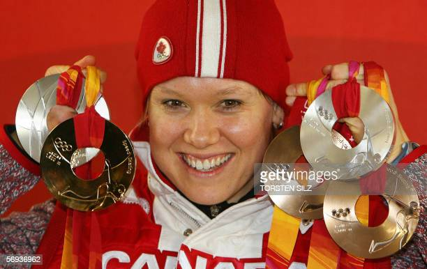 Canadian Speed Skater medallist Cindy Klassen poses with her medals during a 2006 Winter Olympics medals' ceremony in Turin, 25 February 2006. AFP...