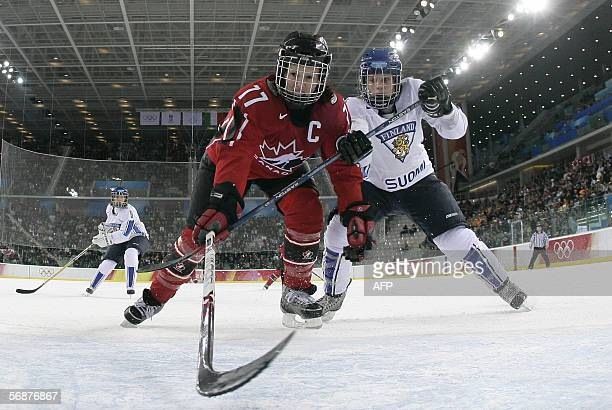 Cassie Campbell of Canada tries to get the puck in front of Saija Sirvio of Finland during the ice hockey women's semifinal Canada vs Finland at the...