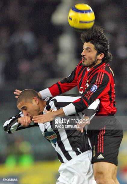 Milan AC's Italian midfielder Gennaro Gattuso and Juventus's French forward David Trezeguet collide as they jump for the ball during their Serie A...