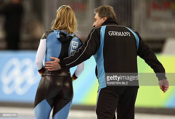 Sabine Voelker of Germany reacts with a member of her team after her race in the Ladies' 1000m speed skating competition during the 2006 Winter...